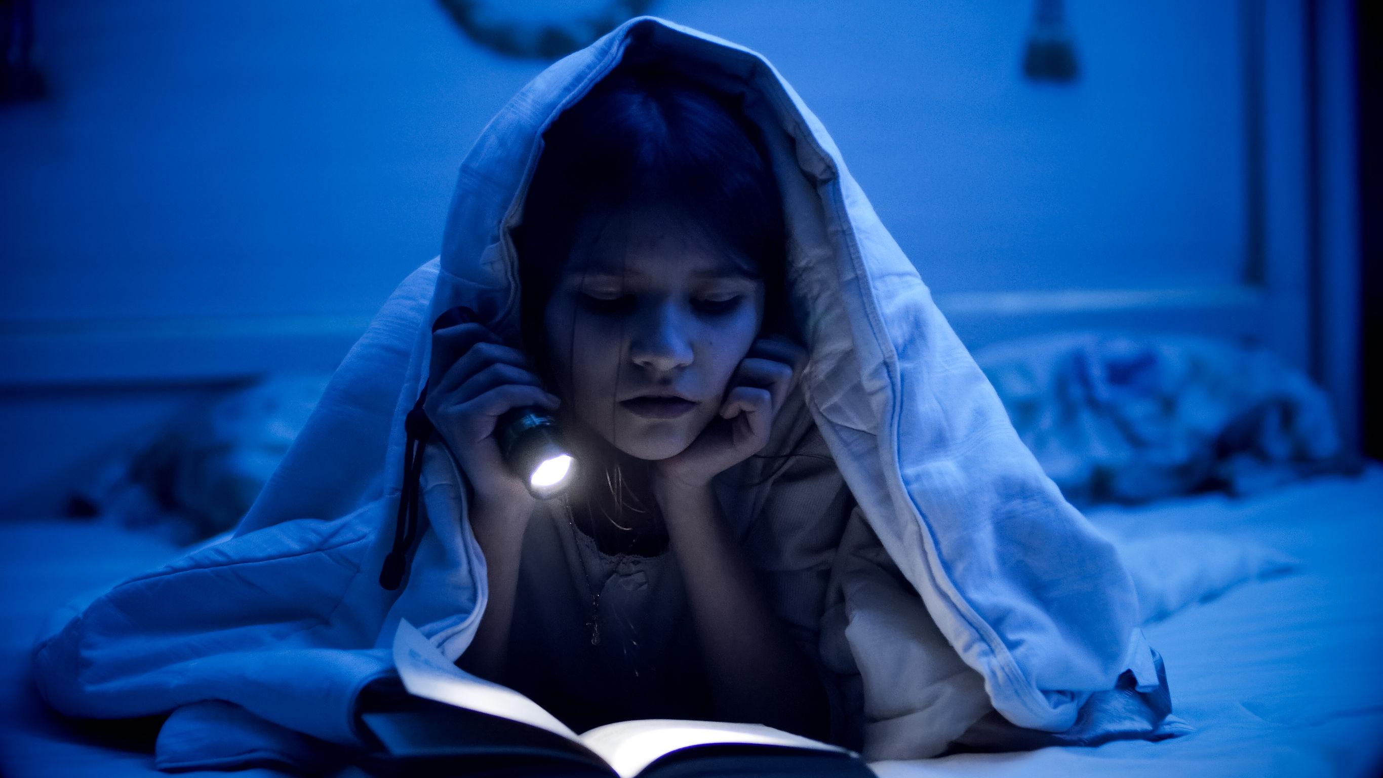 Dziewczynka czyta w nocy